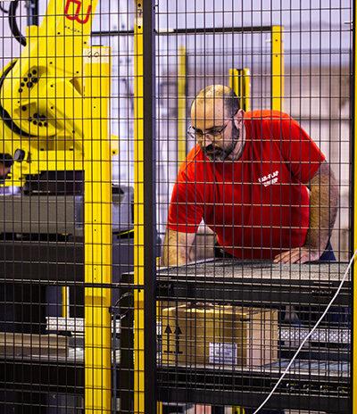 Técnico mecánico ajustando brazo robótico